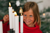Child extinguishing Christmas candles — Stock Photo