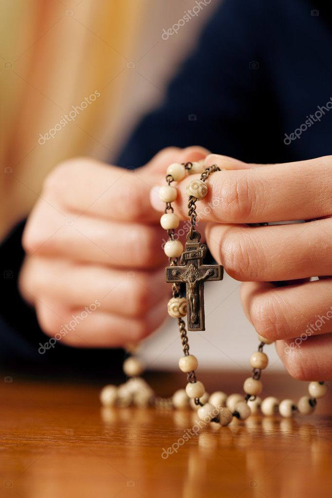 To be seen) with rosary sending a prayer to God, the dark setting suggests she is sad or lonely  — Stock Photo #5051339