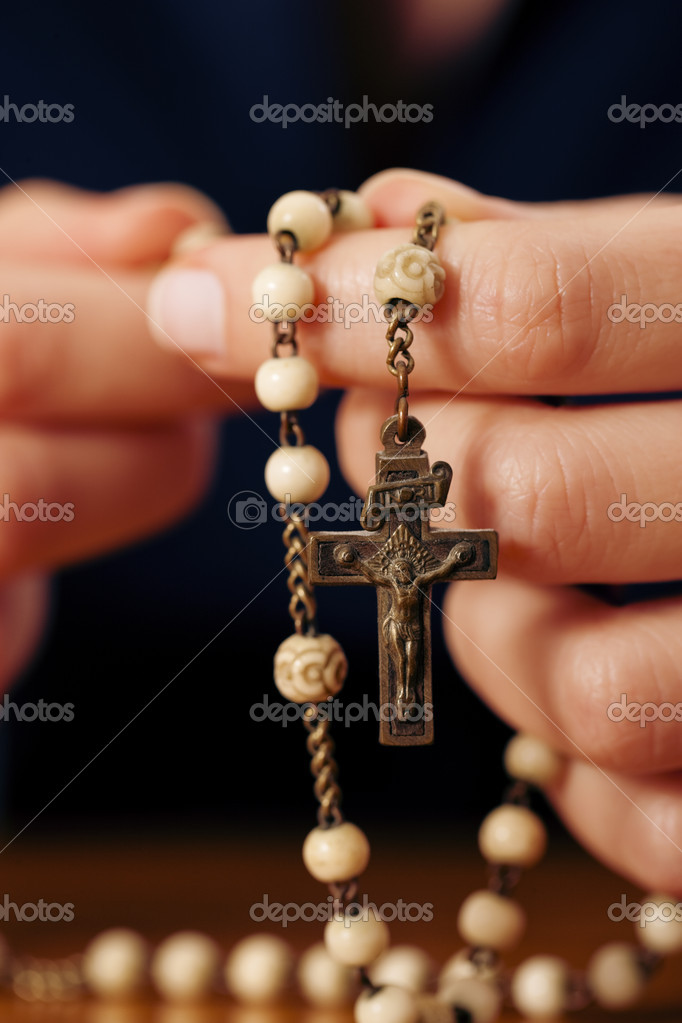 To be seen) with rosary sending a prayer to God, the dark setting suggests she is sad or lonely  — Stockfoto #5051340