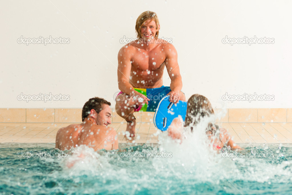 And two men - at a public swimming pool standing under a water gadget — Stock Photo #5051606