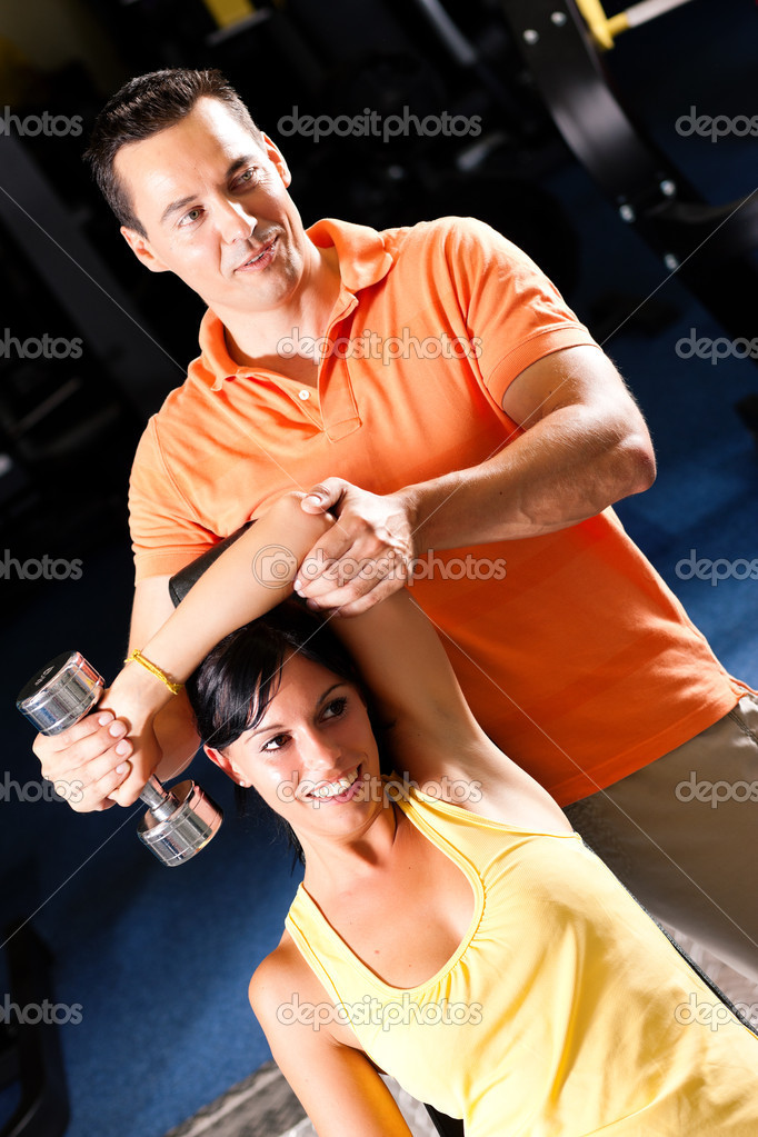 In the gym assisted by her personal trainer (focus on woman)  — Stock Photo #5052502