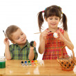 Little children painting the easter eggs - Stock Photo