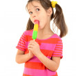 Little girl licking the color ice cream — Stock Photo