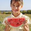 Smiling little girl with slice of watermelon — Stock Photo