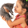 Little girl with gray kitty in hands — Stock Photo