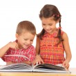 Two smiling children reading the book on the desk — Stock Photo #4886583