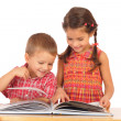 Stock Photo: Two smiling children reading the book on the desk