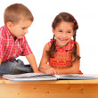 Two smiling children reading the book on the desk — Stock Photo #4886595