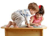 Iki oynayan çocuklara kitap okuma gülümseyerek — Stok fotoğraf