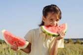 Smiling little girl with two slices of watermelon — Stock Photo