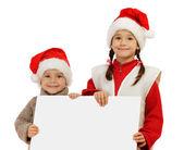 Kleinen Kindern Weihnachtsmützen mit einem leeren banner — Stockfoto