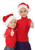 Smiling little children in Christmas hats and thumbs up sign — Stock Photo