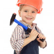 Little smiling builder in coveralls and helmet with hammer — Stock Photo