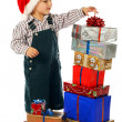 Smiling little boy with lot Christmas gift boxes — Stock Photo