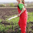 Little girl on field with chopper tool — Stock Photo