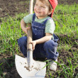 Smiling little boy sitting on field with shovel — 图库照片