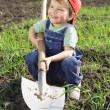 leende liten pojke sitter på fältet med spade — Stockfoto