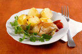 Roasted chicken leg with potatoes on dish — Stock Photo