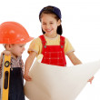 Two smiling little builders planning with liquid level and blueprint — Stock Photo