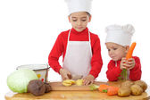 Smiling little chief-cookers on the desk with vegetables — Stock Photo