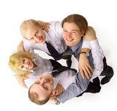 Por encima de la vista de varios socios de negocio feliz mirando a cámara mientras embra — Foto de Stock