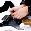 Stock Photo: Person tuning guitar from its headstock over white background