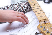 Playing guitar with musical chords in dark room — Stock Photo