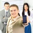 Young businessman talking on mobile standing in office hallway. — Stock Photo #5204741