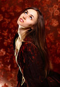 The beautiful young woman on a dark background — Stock Photo
