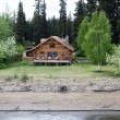 Wooden house at river shore in Alaska — Stock Photo #5039646