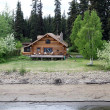 Stock Photo: Wooden house at river shore in Alaska