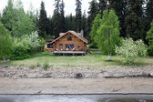 Wooden house at river shore in Alaska — Stock Photo