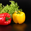 Red and yellow peppers on black — Stock Photo