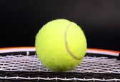 Tennis racket and ball on black — Stock Photo