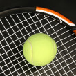 Tennis racket and ball on black — Stock Photo
