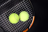 Tennis racket and balls on black — Stock Photo
