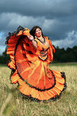 Gypsy girl's dance in a field — Stock Photo