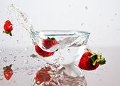 Strawberries falling into the water — Stock Photo