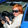 Red-haired womin sun glasses in blue car — Foto de stock #4921888