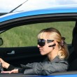 Young blond womin blue car in sun-glasses with hands free bluetooth — Stock Photo #4921912