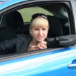 Young blond woman in a blue car. She is smiling happy - Stock Photo