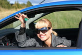 Young blond woman in a blue car with key from it — Stock Photo