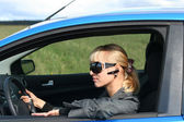 Young blond woman in a blue car in sun-glasses with hands free bluetooth — Stock Photo