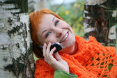 Young red-haired woman in red scarf is talking in mobile-phone — Stock Photo