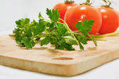 Parsley with tomatoes on a chopping board — Stock Photo