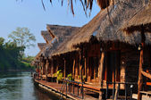 Sunny bungalows in Thailand on river — Stock Photo