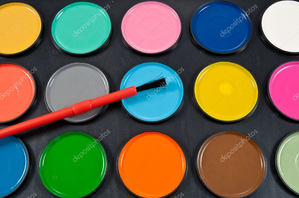 Close up of a fresh dry water colour paint palette complete with red brush — Stock Photo #5281021