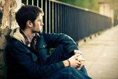 Guy sitting near the fence — Stock Photo