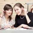 Two young women trying on earrings - Stock Photo