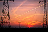 Colorful sunset over pylons, pylon silhuette — Stock Photo